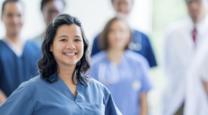 A nurse standing while smiling and looking at the camera, behind her a multi-ethnic group of medical professionals stand together in a hospital building.